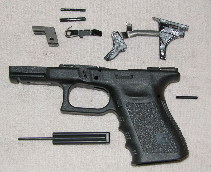 Removing three polymer or steel pins in the correct order allows Glock locking block, trigger housing, and trigger group to be removed. All that is needed is 3/32nd-inch steel punch.
