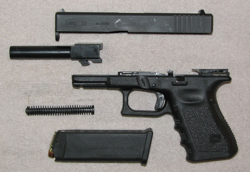 Field-stripped Glock pistol includes slide assembly, receiver/frame, barrel, recoil spring/rod assembly, and magazine. Further disassembly should only be performed by a certified armorer.