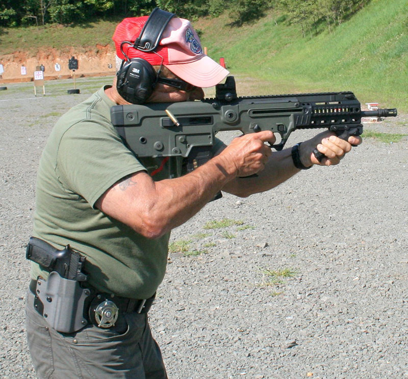 Lieutenant Colonel Martello pounds steel target with fast three-round bursts. X95 is stable and has negligible muzzle climb. Light muzzle makes rifle quite agile. WASP foregrip assists in gun stability, with support hand applying downward and rearward pressure from muzzle end of the weapon.