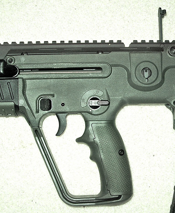 X95's unique parallelogram grip houses new and improved trigger, proximate bilateral magazine releases, safety, and relocated charging lever. Rear metal BUIS is visible.