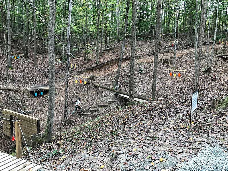 EST deputy charges through assault course with sidearm. Hits were required before advancing, and performance was timed. Steel targets on other side of road are situated for long-gun training. Flat trajectory and plunging fire challenges are evident.