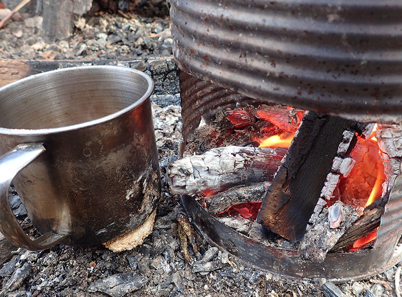 Coffee cups and some food can be warmed as stove dies down due to radiant heat and glowing coals. Fire is easy to start up again when more fuel is added.