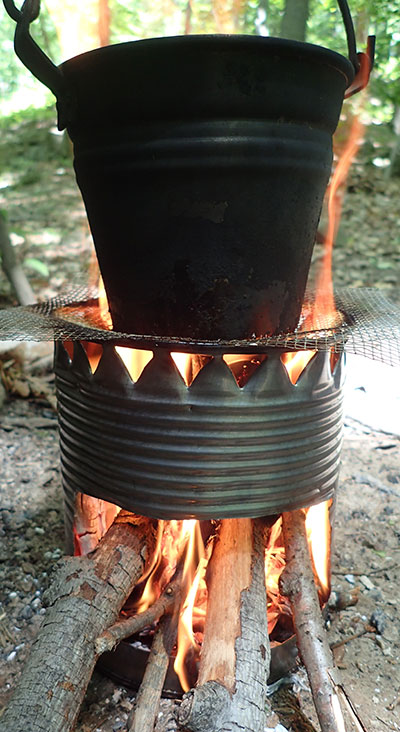 Kettle or pot can be used to boil on top of hobo stove supported by wire fencing or grill. Slide fuel in the side port and push it in as it burns.