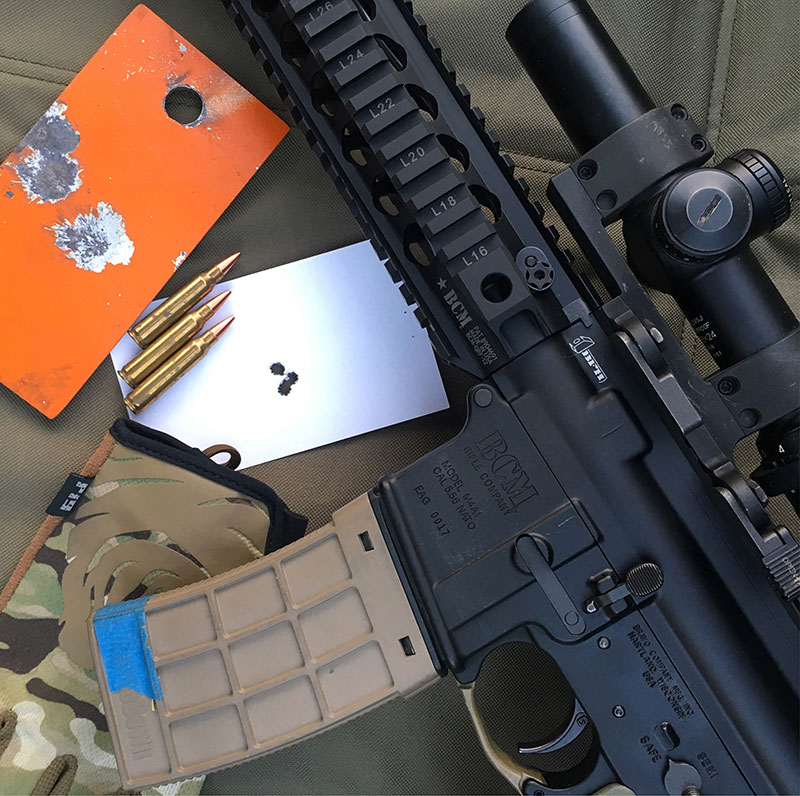"Steel plate and index card shot from standing barricade with BCM QRF upper and Black Hills Match ammo. Keeping shots on 3x5-inch target at 100 yards standing is no great feat with proper technique. One-hole group was a great and welcome surprise, but as they say in fine print on weight-loss commercials, ""Results not typical."""