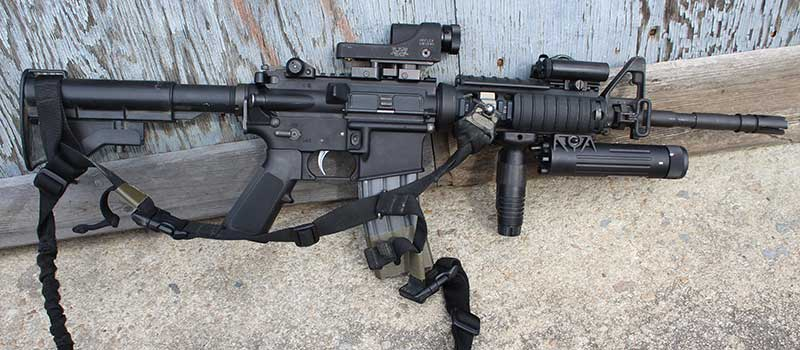 Author's clone of his initial issue 1998 SOPMOD Block I carbine. AR is outfitted with Trijicon Reflex Sight, authentic SOPMOD I CVL-100 PEQ-5 laser, Insight VLI, Knight's Armament RAS rail with VFG, back-up rear sight, and sling mount.