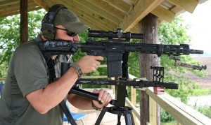 James Ferguson shoots SR-25 E2 ACC from Spec Rest, which clamps rifle into position and holds it firmly in place. This allows rifle to be comfortably and accurately shot from standing.