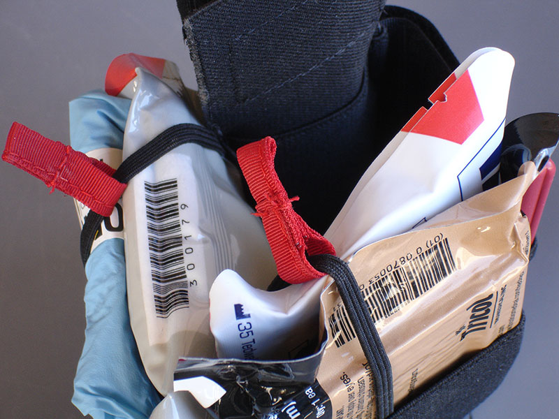 Fully loaded Ankle Trauma Kit. It has a compartment for a tourniquet (C-A-T or SOFTT-W compatible), two separate compartments for hemostatic gauze, compact pressure bandages, gloves, chest seals, etc. Additional small pocket holds either a marker or chest decompression needle. Elastic bungee cords keep medical components secure. Red pull tabs similar to pull tabs on open-top magazine pouches allow quick and easy access.