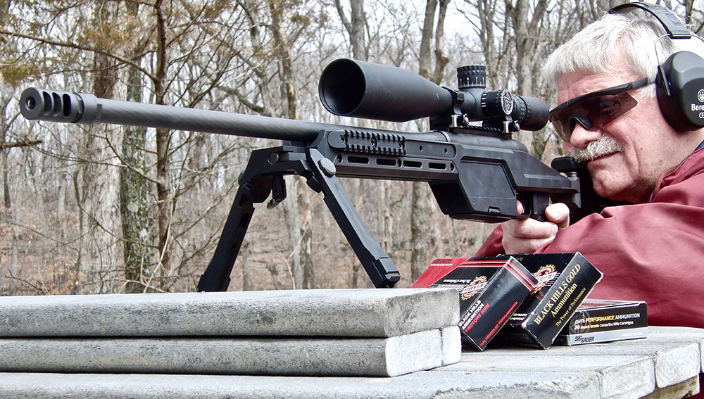 Thompson shoots SSG 08 .300 Win Mag from the bench.