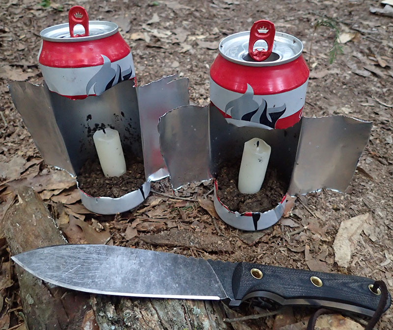 Two discarded beer cans were made into camp lanterns by cutting H shape into the cans and opening them up. Wings can be adjusted to act as wind covers.