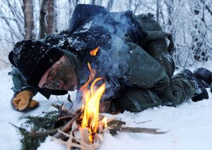 U.S. Air Force officer builds fire to help combat frostbite and hypothermia during SERE exercise. Knowing how to build a fire is one of the most important survival skills. Photo: U.S Air Force