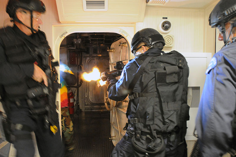 Los Angeles Police Department D Platoon (SWAT) team members breach room and engage hostile targets in training exercise focused on visit, board, search, and seizure tactics aboard maritime vessels. D Platoon was one of first U.S. law enforcement tactical teams to employ NFDDs. Photo: U.S. Navy photo by Mass Communication Specialist 3rd Class Kristopher Kirsop / Released