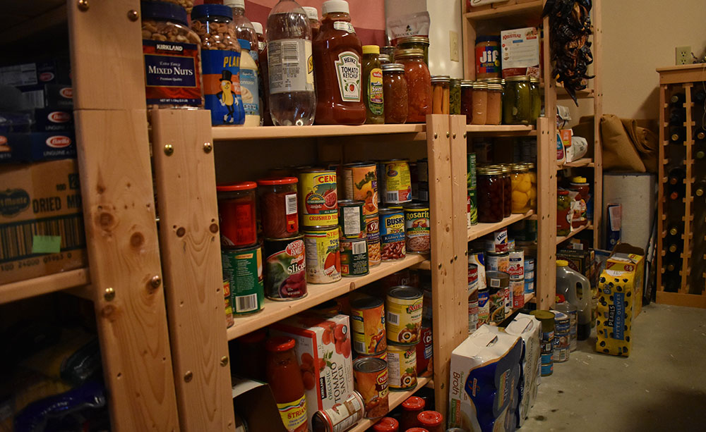 Portion of author's pantry, with home and commercially canned food.