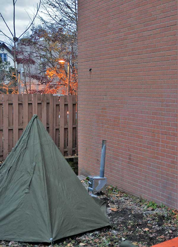 At dusk, author set up Polish Tarp Shelter with opening facing the brick wall and a woodburning stove. At night, shelter will be nearly impossible to see.