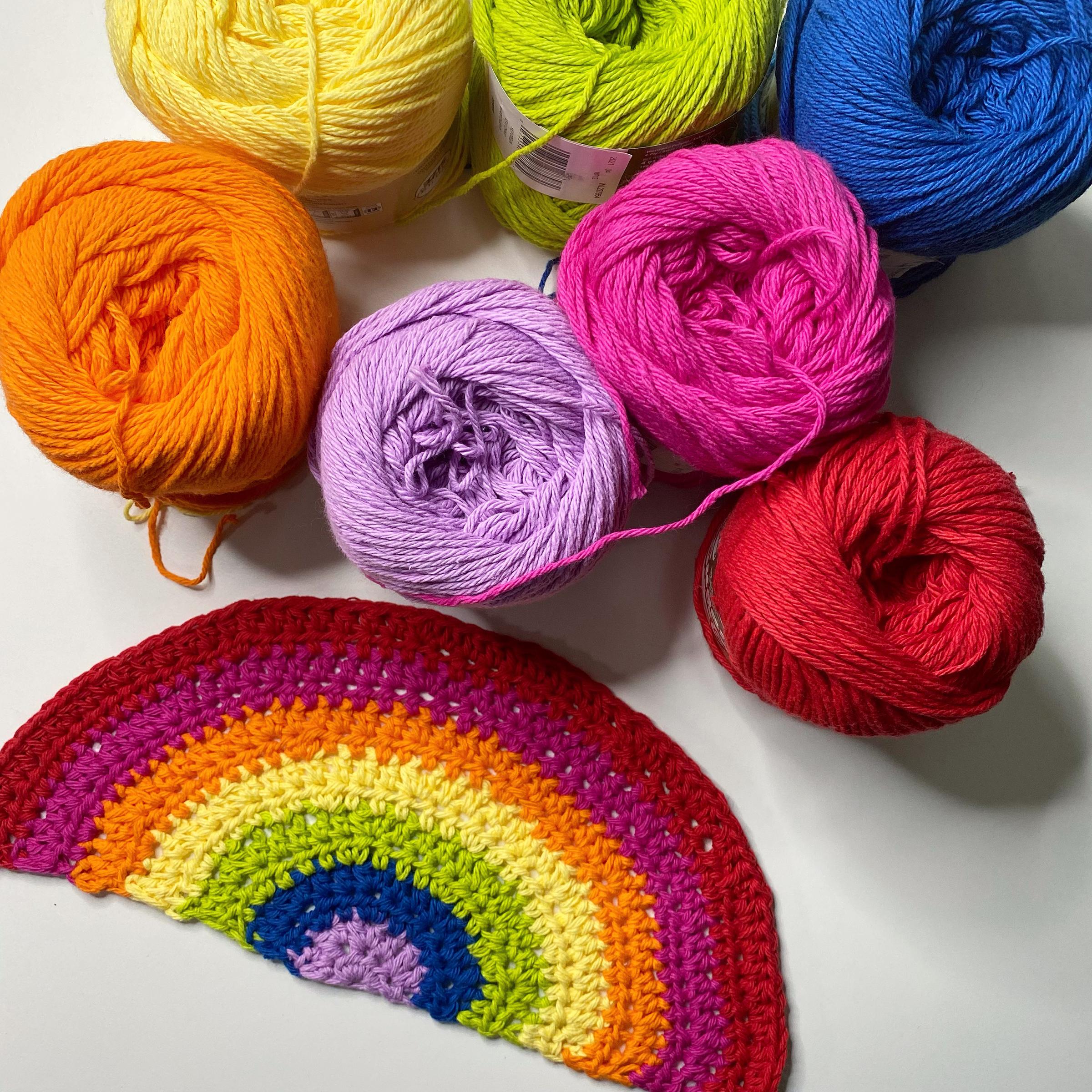 crocheted rainbow beside colorful yarn