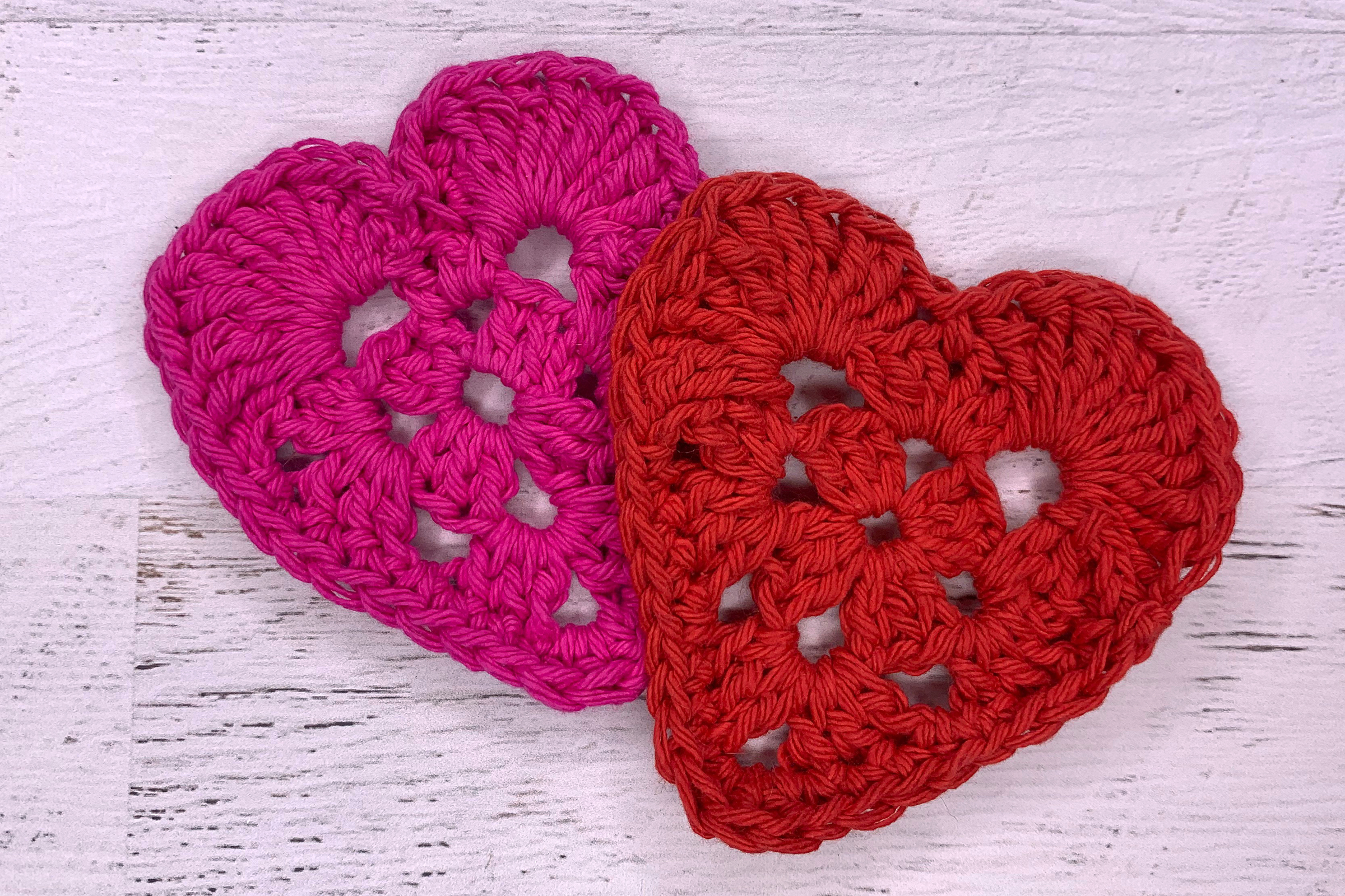 two red crocheted granny hearts