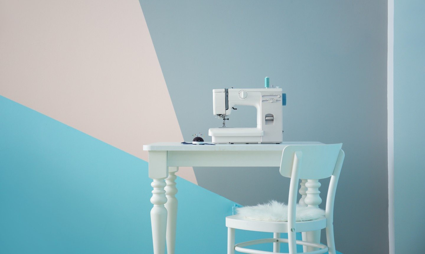 sewing machine in front of geometric painted wall