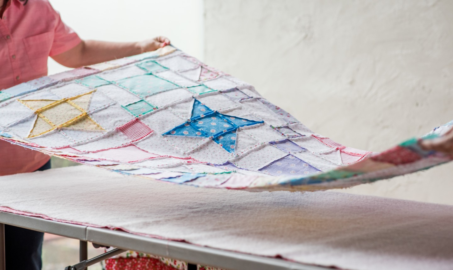 woman laying out quilt top