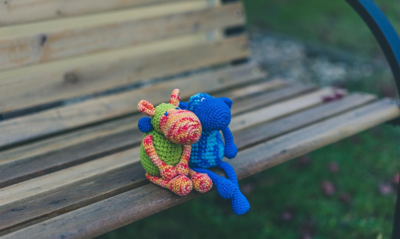 amigurumi figures on a park bench