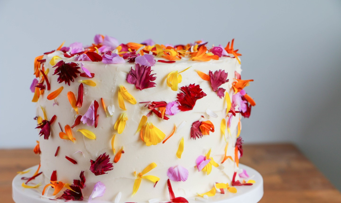 white cake covered in flower petals