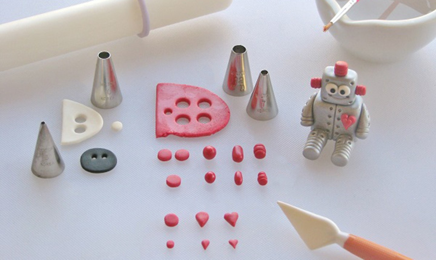 adding red fondant accents to robot
