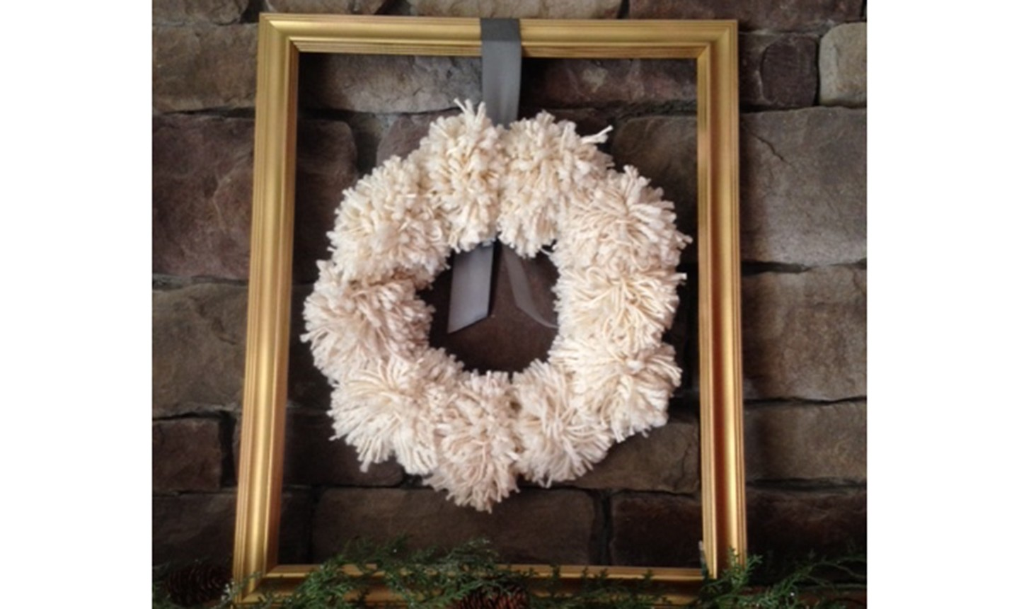 white pom pom wreath in a frame