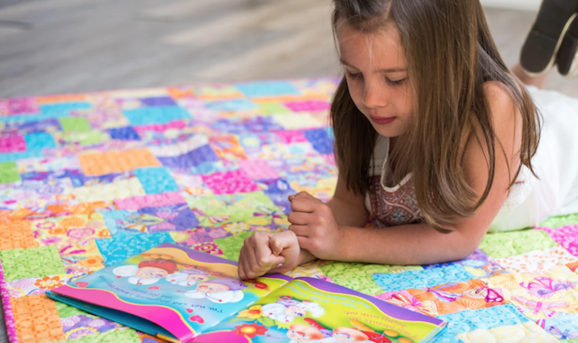 child reading on a quilt