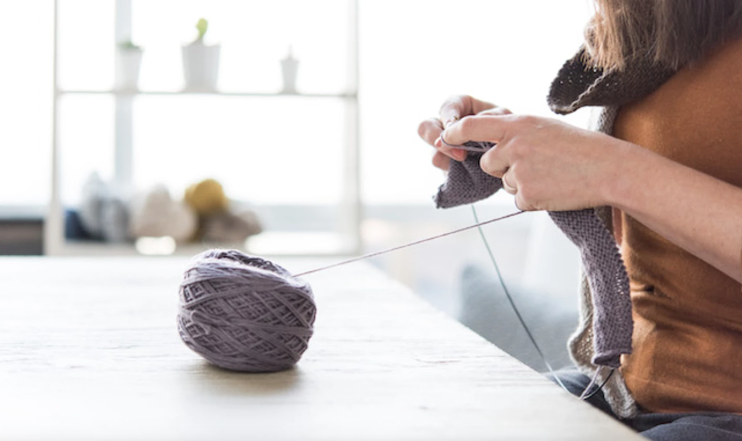 woman knitting from purple yarn
