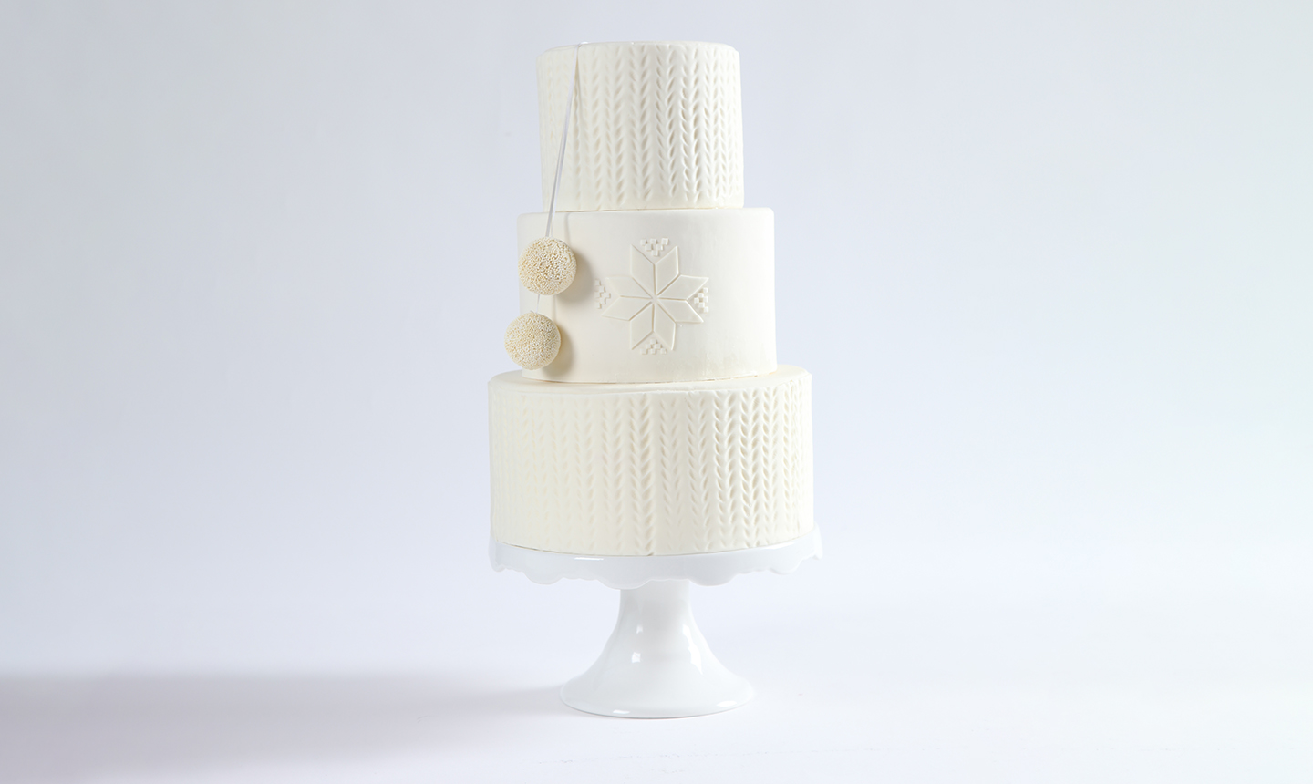 three tiered winter white cake with a snowflake and pom pom design