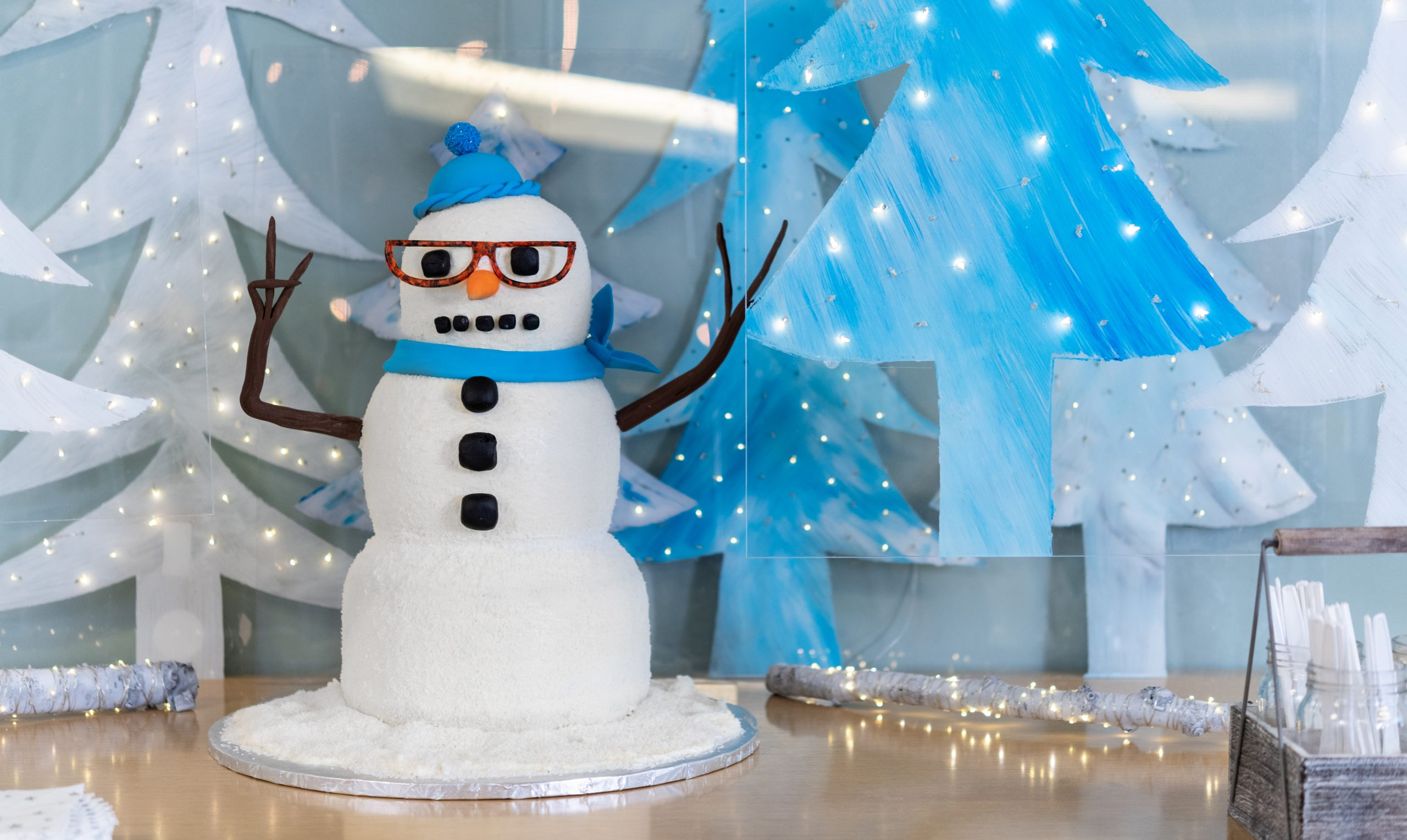 three tiered snowman cake with glasses a hat and scarf