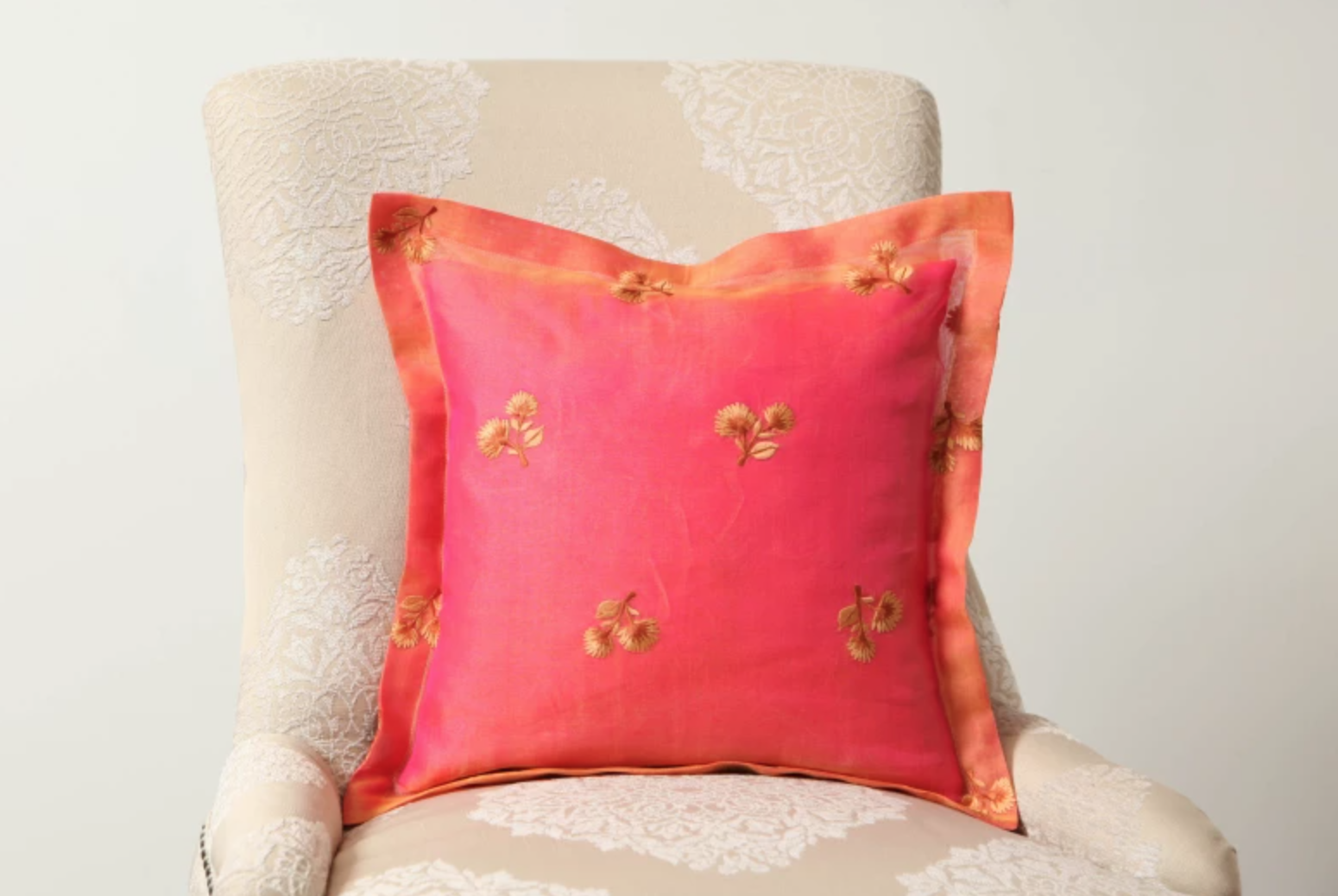 pink and orange sewn pillow on a cream chair