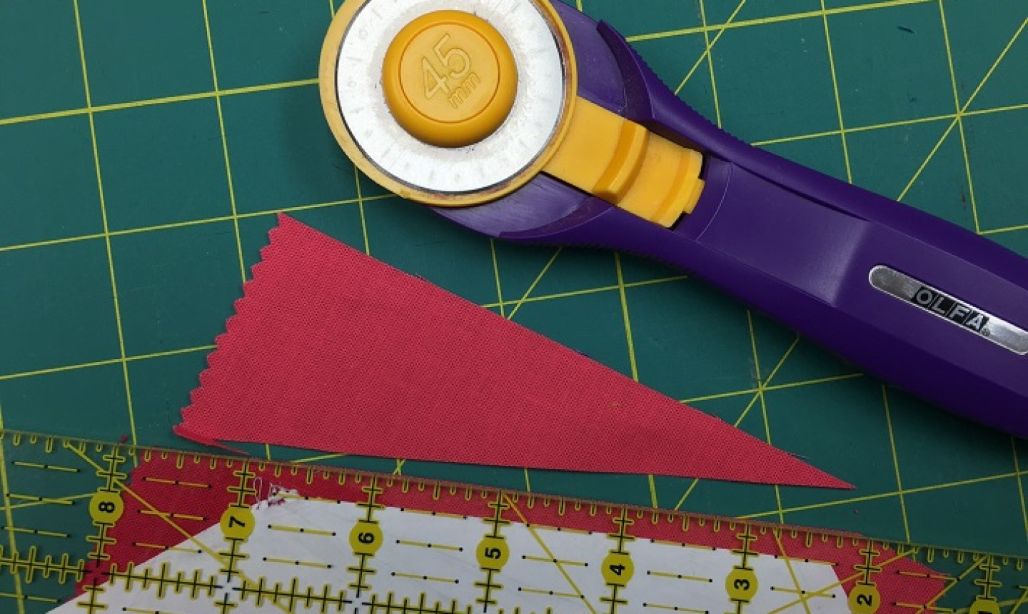 rotary cutter with cut red fabric strip