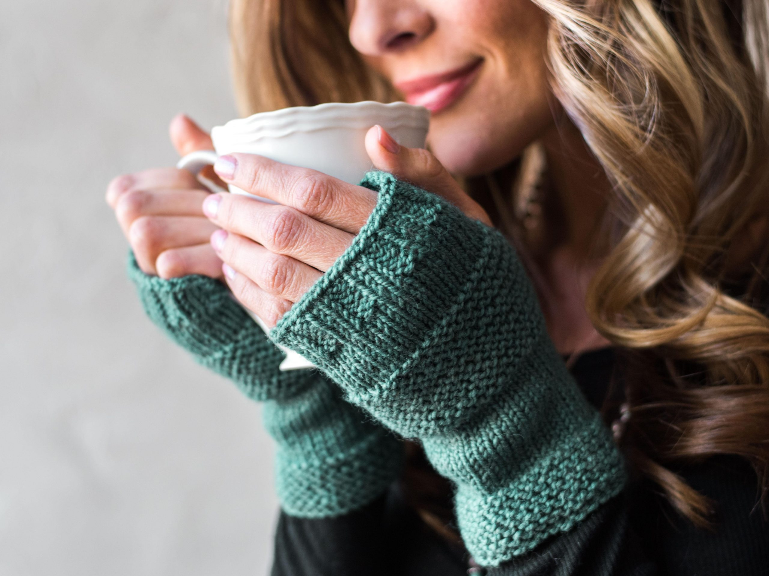 Woman wearing green fingerless gloves