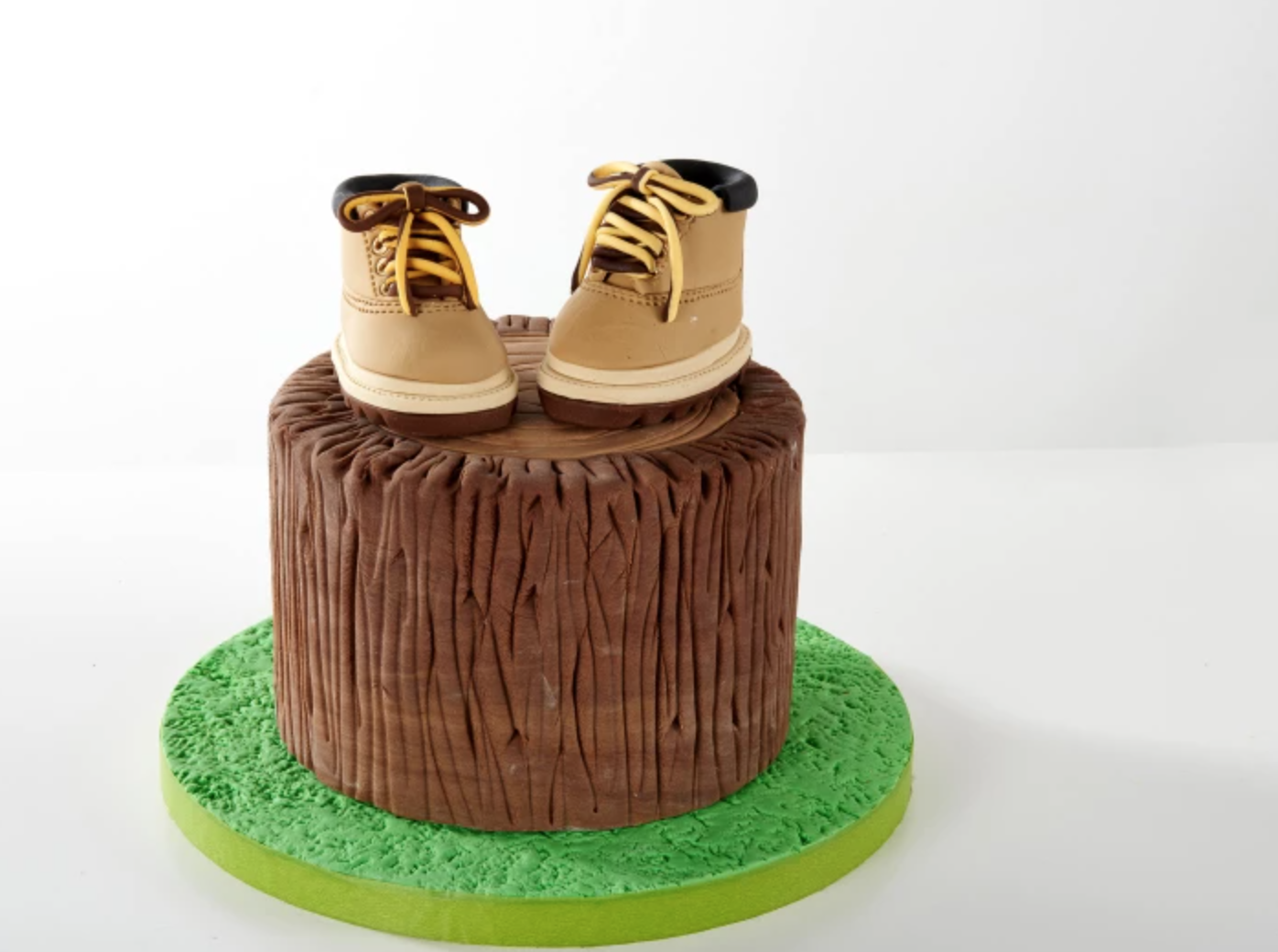 sculpted tree stump cake with little shoes