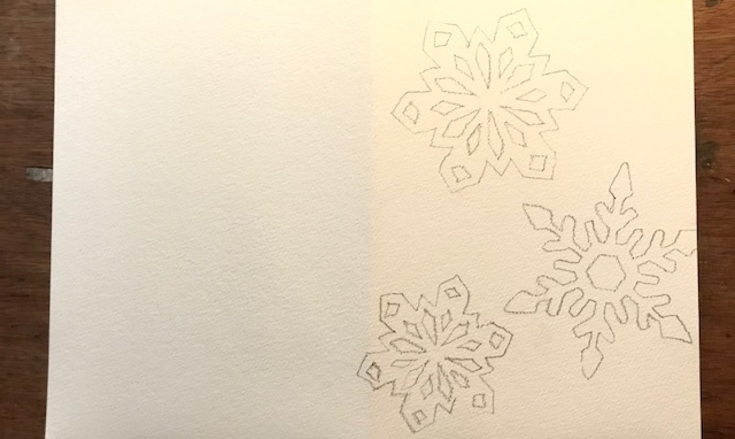 watercolor paper with snowflakes drawn in graphite