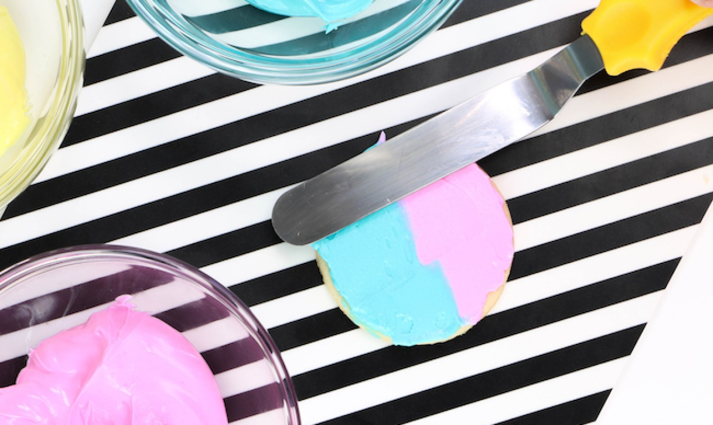 using an offset spatula on a blue and pink cookie