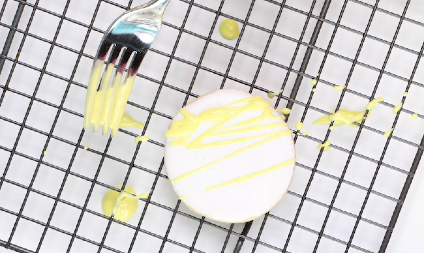 drizzling yellow royal icing on a cookie