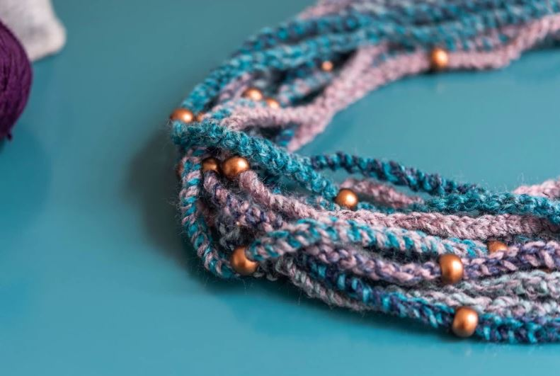 Crocheted necklace with beads on a teal background