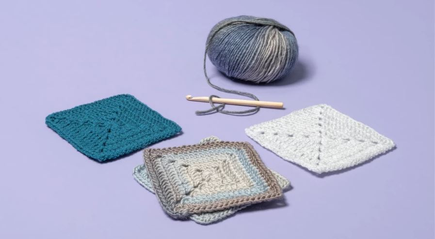 Four crocheted granny squares on lavender background with crochet hook and yarn in background