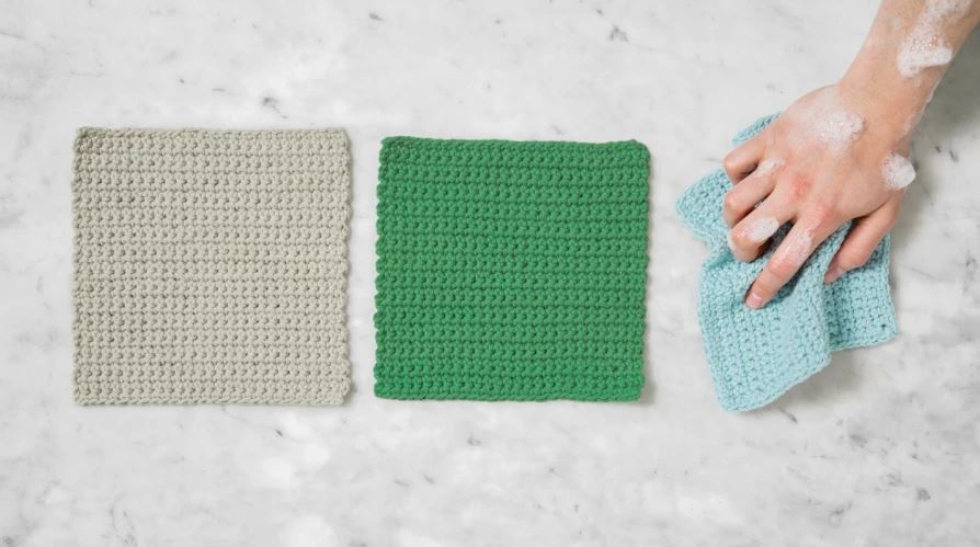 three crocheted dishcloths in tan, green and light blue. The light blue cloth is scrunched up in a hand, covered in suds.