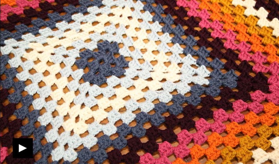 Tight shot of bright, colorful granny square afghan
