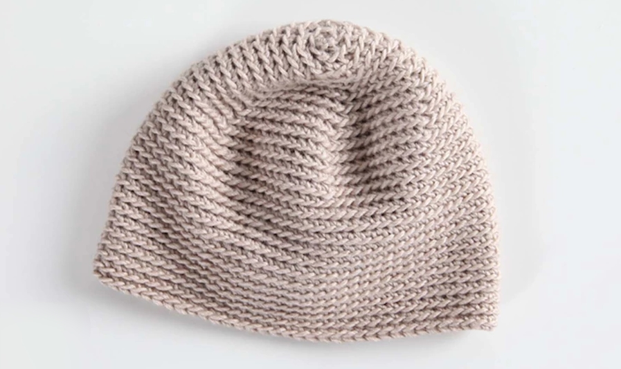 Tan crocheted beanie laid flat on a white background