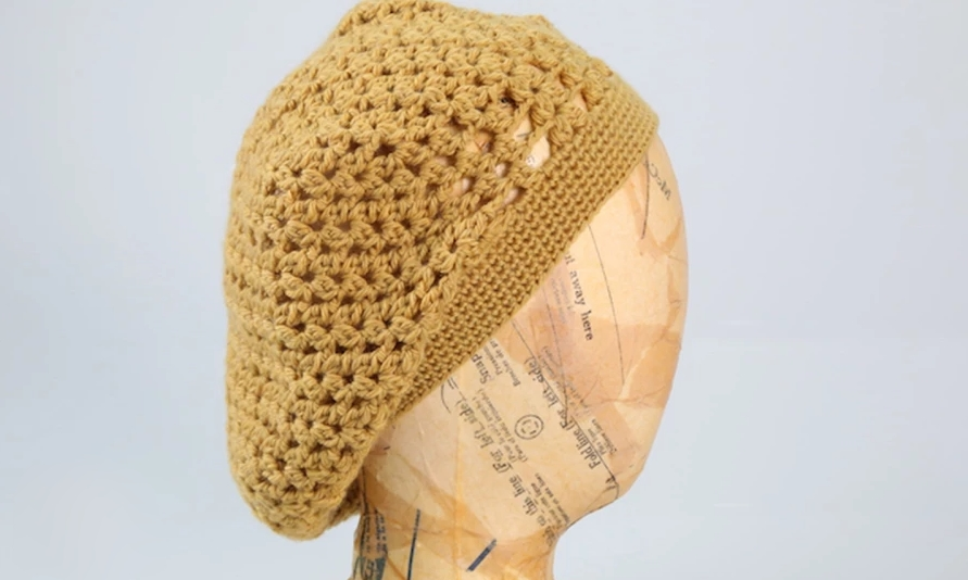 Yellow crocheted beret on a mannequin head