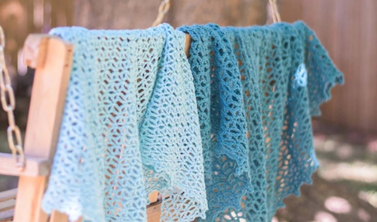 Two blue crocheted shawls draped over the back of a wooden porch swing