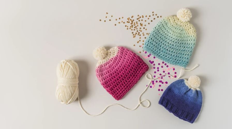 Pink, light blue, and dark blue ombre hats with pompoms on a white background with a skein of white yarn and confetti surrounding the hats.