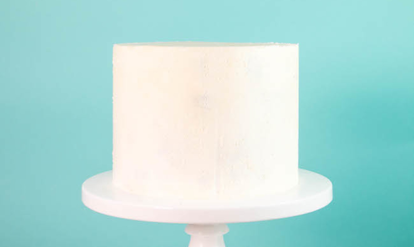 Cake with white frosting on a pedestal
