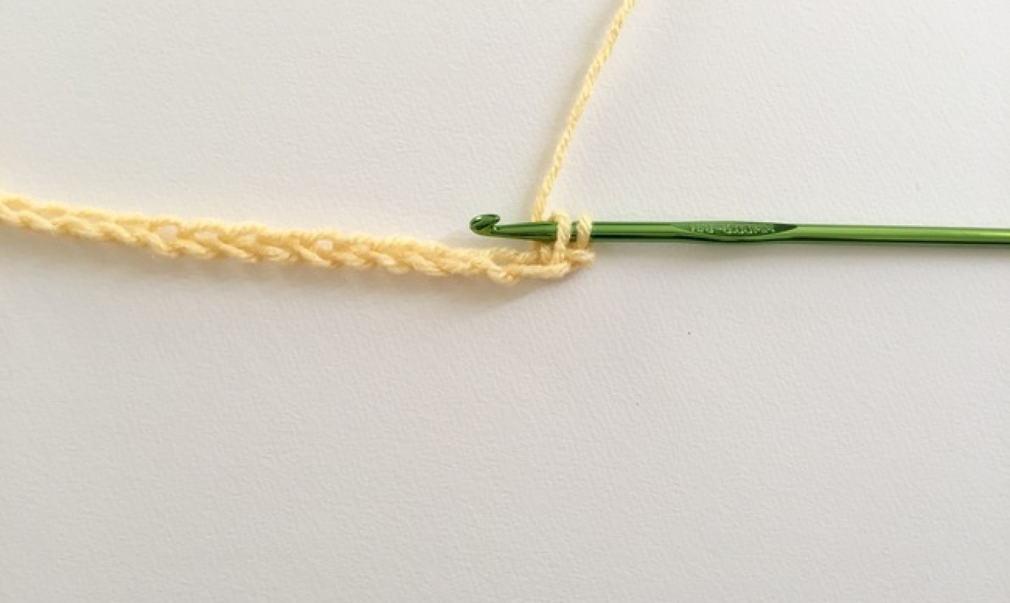Chain of yellow yarn with green hook