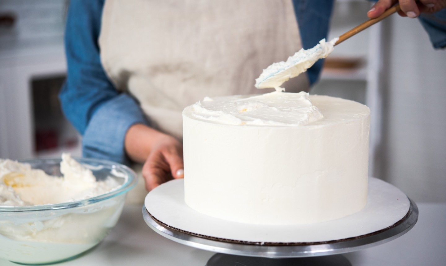 putting frosting a cake