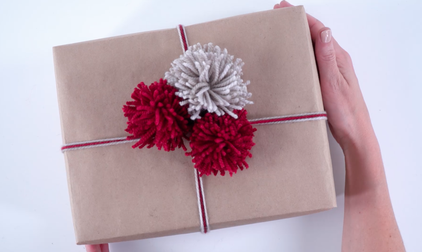gift wrapped with yarn pom poms