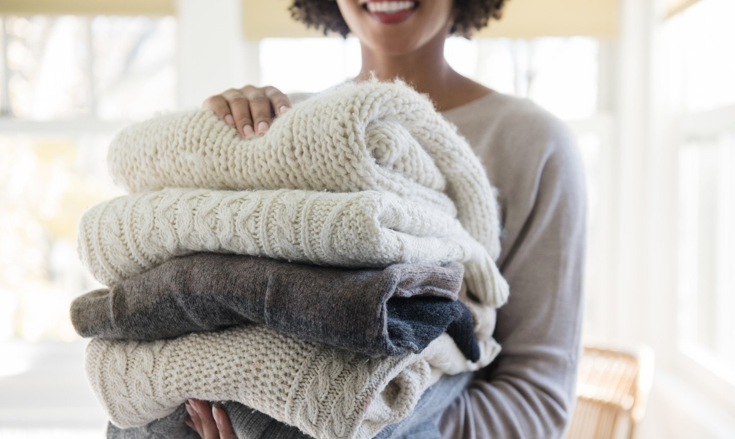 woman holding folded sweaters