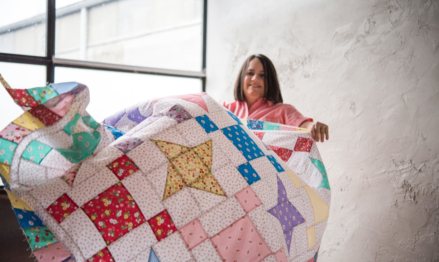 woman draping quilt top